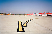 The Hawk jet aircraft of the elite 'Red Arrows', Britain's prestigious Royal Air Force aerobatic team, are lined up at RAF Akrotiri, Cyprus as members of the team's ground crew step away from the aircraft that they respectively look after. From a low angle we see a wide landscape looking over the taxi-way markings that direct military airplanes. The Red Arrows aircraft are a deep red colour that stand out against the horizon in an identical line. It is a wide expanse of road surface, the yellow centre-lines are for the benefit of pilots who need guidance for parking areas after landing, or leaving towards the departing runway on the southern part of the Cypriot Mediterranean island. With the Red Arrows, the nine taxiing jets all peel off in unison to and from the parking area and these lines are vital for this technique.
