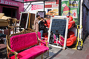 Buyers inspect red sofas with other bright furniture on sale in a London street.