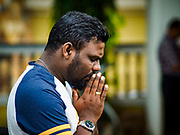 08 OCTOBER 2017 - NEGOMBO, WESTERN PROVINCE, SRI LANKA:  Men stand outside a Catholic church and pray during Sunday mass in Negombo. About 8% of Sri Lanka is Christian, the majority of which are Roman Catholic. Catholicism was spread by Portuguese colonizers who came to Sri Lanka in the 1500 and 1600s.  PHOTO BY JACK KURTZ