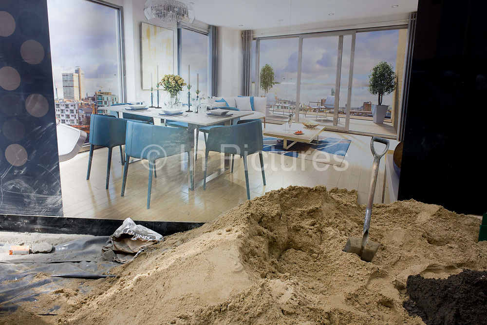 Construction hoarding showing apartment interior and shovel with sand for making concrete. The poster is on a screen hiding the workings of construction and mess to street life outside. The mound of sand ballast and fine aggregate with the shovel embedded in the materials appear to be part of the same picture behind - the living space of a modern lifestyle high above the city whose floor is the same colour and hue of the sand.