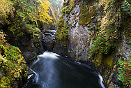 The Lower Englishman River Falls in Englishman River Falls Provincial Park near Nanaimo, British Columbia, Canada.  In the Spring when the water levels are higher the waterfall goes over, not under this rock.