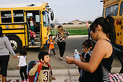 Gerardo Ramirez Hernandez, 6, bottom center, talks to his mom, Leticia Hernandez after he and his sister step off the bus after school. The Hernandez family lives in Madera, California and received solar panels from Grid Alternatives.