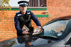 PCSO Mike Matthews places a Wanted Poster for Nick De Mota on the windscreen of a car in Sheffield  as part of the South Yorkshire Police Operation Lockdown, targeting vulnerable vehicles and offering advice to help raise awareness about the risks of leaving cars Ôvulnerable.Õ <br /> <br /> 26 November 2013<br /> Image © Paul David Drabble<br /> www.pauldaviddrabble.co.uk