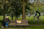 An old (high risk) lady sits on one of the taped up benches - Clapham Common is pretty quiet now as it is colder and Lambeth Council has taped up all the benches, put up signs and organised patrols by wardens. The 'lockdown' continues for the Coronavirus (Covid 19) outbreak in London.