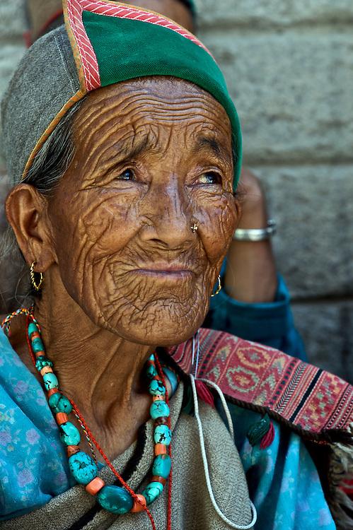 An elderly Kinnauri woman wearing the traditional hat and jewelry of her people. The Kinnauri people live in Himachal Pradesh, North India