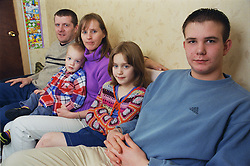 Family group sitting together on sofa,