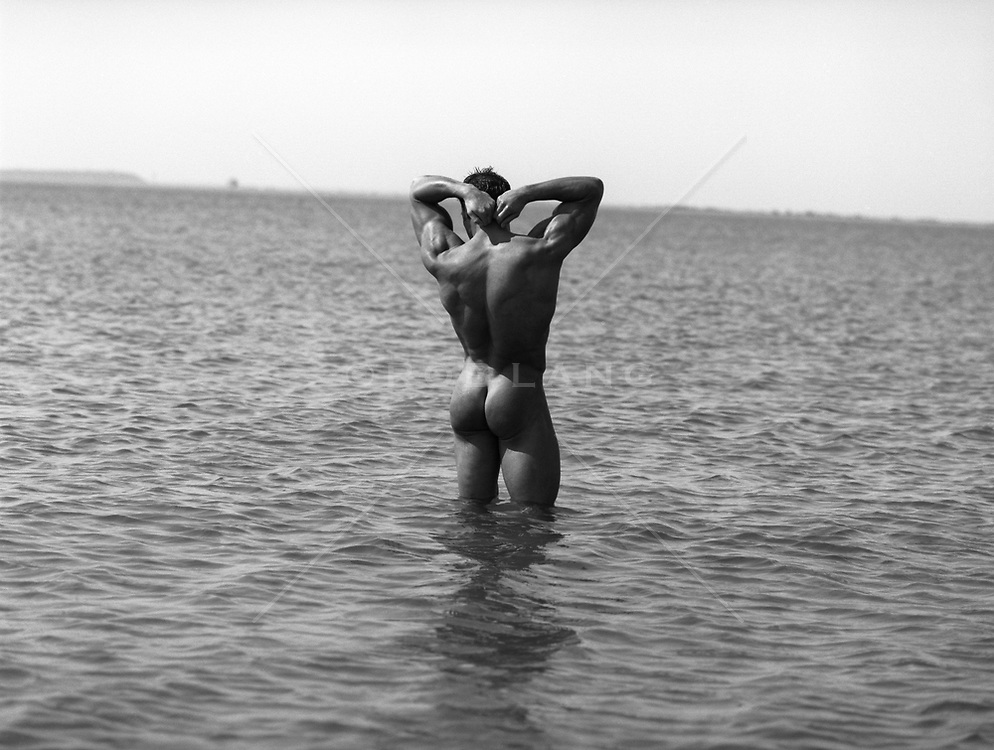 rear view of a male body builder standing in shallow water in East Hampton, NY