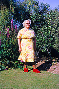 Family portrait full length grandmother in floral dress standing in garden, British culture 1967 wearing red slippers