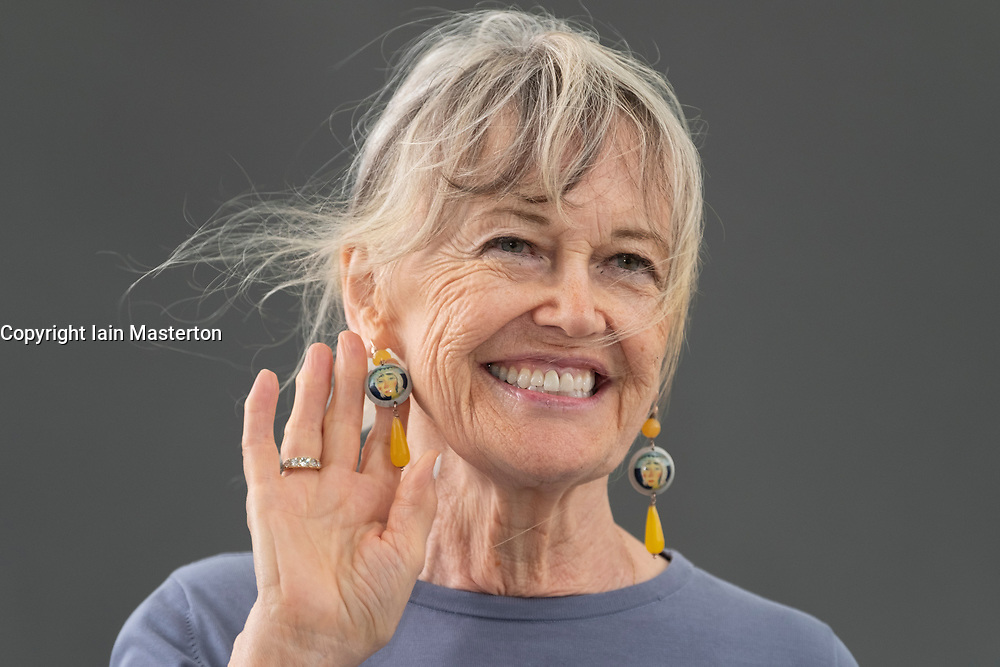 """Edinburgh, Scotland, UK; 17 August, 2018. Pictured; Helen Bellany, ( displaying earrings using her husband's paintings) widow of artist John Bellany, talks about the mystery, poetry and passion that was at the core of their life together in  her book """"The Restless Wave""""."""
