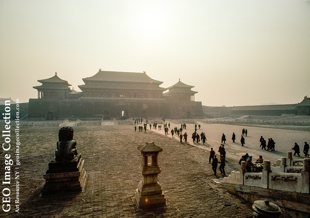 The huge Gate of Heavenly Peace, the main entrance to the Forbidden City, looms in the dusty early morning haze which partially obscures the sun.  This view, taken from Tiananmen Square, shows the tiny figures of people walking along the main thoroughfare leading to the gate.  In the foreground are a large bronze lion an d a stone Oriental lantern.