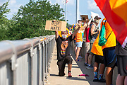 """Issac holds a sign reading """"stop the hate"""" while kneeling during the Milton Pride Rally in Milton, Pennsylvania on August 8, 2020. The I Am Alliance organized the event after a local grocery store posted an anti-mask sign which blamed the LGBTQ community for spreading COVID-19.(Photo by Paul Weaver)"""