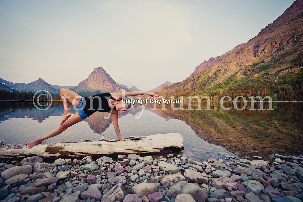 woman yoga outdoors in the mountains on two medicine lake, glacier national park