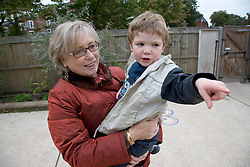 Grandmother picking young boy up from nursery,
