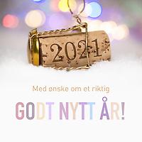 Nyttårshilsen i form av Champagne-kork med innpreget årstall 2021, tekst «Med ønske om et riktig godt nytt år!».