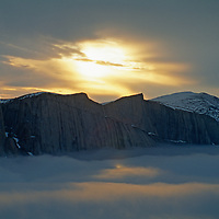 The midnight sun circles over fog and cliffs above the Stewart Valley