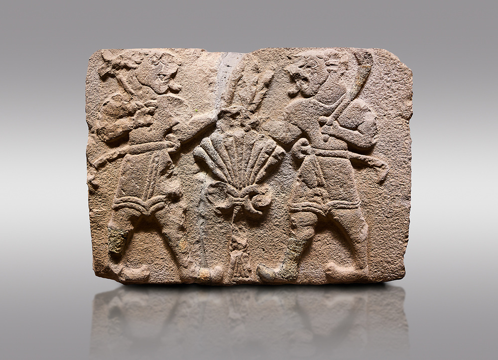 Aslantepe Hittite relief sculpted orthostat stone panel of Lion Men. Limestone, 1399-1301 BC. Anatolian Civilisations Museum, Ankara, Turkey.<br /> <br /> There are two lion-men with a sword at their waists on both sides of the tree of life. The figure on the right holds a sickle in his left hand resting on his shoulder and a symbol his right hand. The figure on the left carries a double-faced ax in his right hand. <br /> <br /> Against a gray background. .<br /> <br /> If you prefer to buy from our ALAMY STOCK LIBRARY page at https://www.alamy.com/portfolio/paul-williams-funkystock/hittite-art-antiquities.html . Type - Aslantepe - in LOWER SEARCH WITHIN GALLERY box. Refine search by adding background colour, place, museum etc.<br /> <br /> Visit our HITTITE PHOTO COLLECTIONS for more photos to download or buy as wall art prints https://funkystock.photoshelter.com/gallery-collection/The-Hittites-Art-Artefacts-Antiquities-Historic-Sites-Pictures-Images-of/C0000NUBSMhSc3Oo