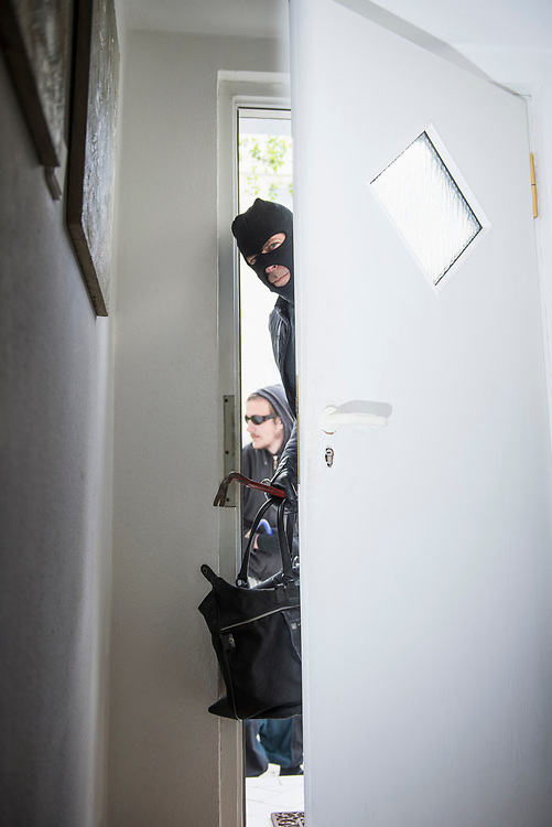 Burglar breaking into a home with crowbar and bag through door
