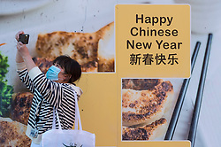 © Licensed to London News Pictures. 05/02/2021. LONDON, UK. A woman wearing a facemask takes a photo next to construction hoarding in Chinatown ahead of the Chinese New Year festival, the Year of the Ox.   The normal parade and festivities have been cancelled this year due to the ongoing coronavirus pandemic and the organisers will instead host celebrations online.  Photo credit: Stephen Chung/LNP
