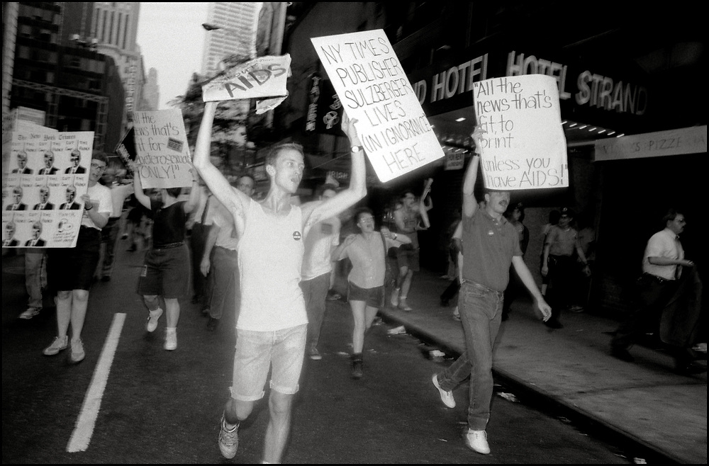 """On July 25, 1989, 150 members of ACT UP demonstrated in front of New York Times publisher Punch Sulzberger's residence at 1010 Fifth Avenue and then marched to West 43rd Street offices of the paper. After threatening a sit-in in Times Square, the protesters were finally allowed to picket on the sidewalk opposite the Times. Several demonstrators held a die-in in front of the building. <br /> <br /> The demo was preceded by a Sunday zap in which outlines of dead bodies were stenciled on the streets around Sulzberger's pad, and the neighborhood decorated with stickers emblazoned, """"All the News That Kills."""" <br /> <br /> """"AIDS Crisis Escalates While N.Y. Times Sleeps"""" was the headline on the leaflet ACT UP distributed, which asked:  """"Why, instead of actively investigating the work of federal health organizations, does the Times merely rewrite [their] press releases? ... Such compliance makes the Times a mere public relations agent for an ineffective government.... Why did the Times, in its June 29 editorial (Why Make AIDS Worse Than It Is?) dismiss a new federal study finding a 33% under-reportage of AIDS infections in the US?  This callous editorial assured its general readership that AIDS will be over soon, once infected members of undesirable risk groups die off."""""""