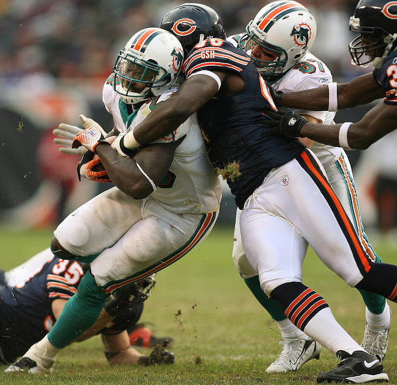 Chicago Bears vs Miami Dolphins at Soldier Field  - Miami's Ronnie Brown (23) , middle, is tackled by Chicago's Alex Brown (96) in the fourth quarter.  At right are Miami's Justin Peelle (87) and Chicago's Charles Tillman (33)..