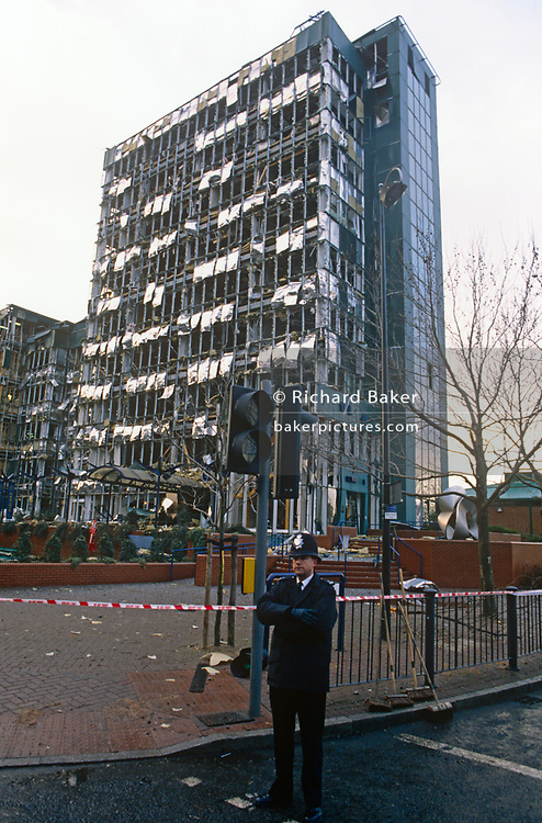 A Met police officer stands at the scene of the IRA bombing in London Docklands, detonated by Irish Republicans and resulting in the deaths of two people and more than 100 injured, some permanently, on 10th February 1996, in London, England.