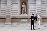 Two young men take pictures of each other beneath statues of reknowned men outside the Royal Academy of Arts on 5th March 2021 in London, England, United Kingdom. The opposite figures gives a juxtaposition of the vastly different eras.
