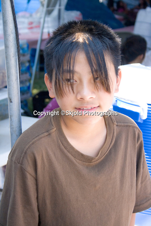 Young cool Hmong boy with long bangs over eyes. Hmong Sports Festival McMurray Field St Paul Minnesota USA