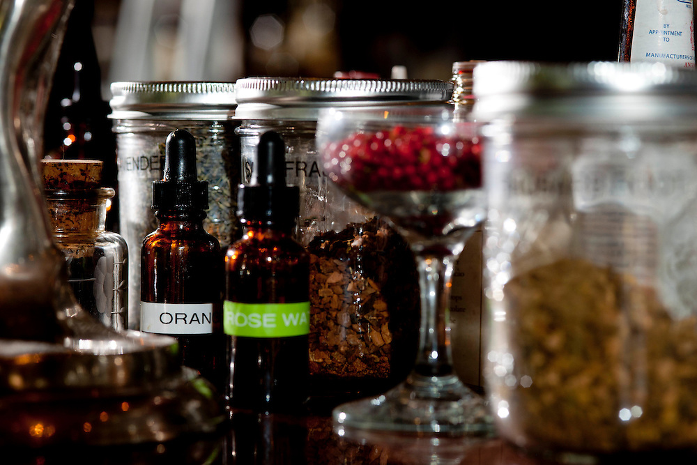 Close-up view of a small section of the bar set-up at Peche's Restaurant and Bar. Orange bitters and rose water in brown bottles with droppers in front of dried ingredients in jars.
