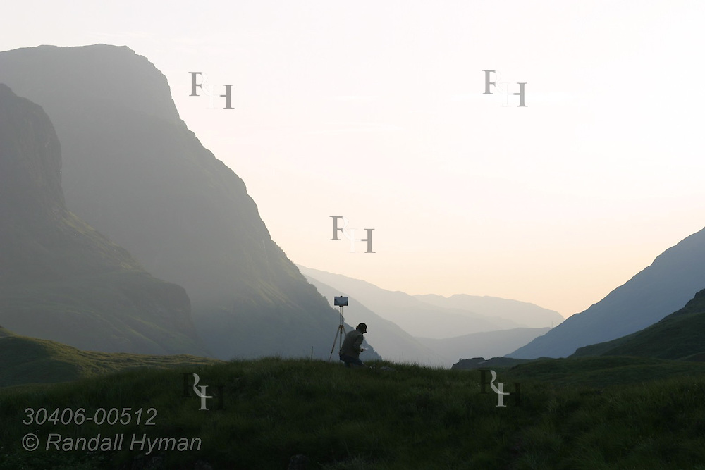 Silhouetted artist paints mountain scene in saddle of upper Glen Coe on a July eve; Glencoe, Scotland.