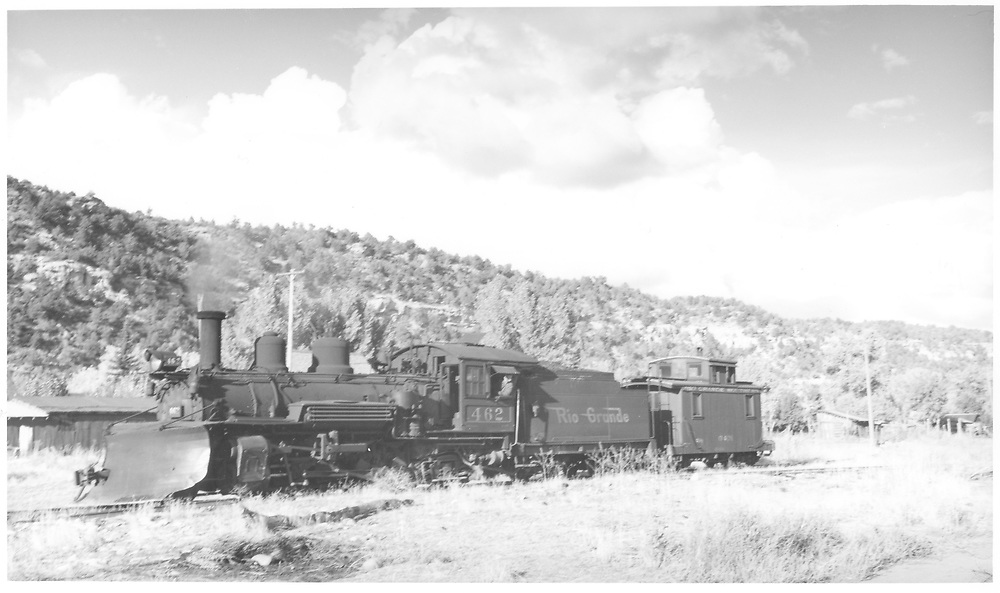 """3/4 fireman's-side view of leased D&RGW #462 with wedge plow and RGS caboose 0401 on north end of Dolores yard.<br /> RGS  Dolores, CO  Taken by Richardson, Robert W. - 10/10/1945<br /> In book """"Rio Grande Southern II, The: An Ultimate Pictorial Study"""" page 316<br /> Also in """"RGS Story Vol. VII"""", p. 183.   Same as RD109-079.<br /> Thanks to Don Bergman for additional information."""