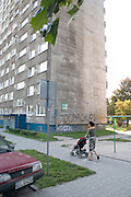 Mom wheeling baby to Bloc housing a reminder of the Communist era. Balucki District Lodz Central Poland