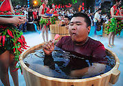 HANGZHOU, CHINA - JULY 20: <br /> <br />  A man sitting in an ice bucket eats pepper ice-creams during a competition at Song Dynasty Town on July 20, 2016 in Hangzhou, Zhejiang Province of China. As the ground temperature reached 40 degrees Celsius in Hangzhou, tourists competed eating peppers while sitting in the ice buckets to feel hot and cool at the same time in the Song Dynasty Town scenic area. <br /> ©Exclusivepix Media