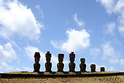 Easter Island (Rapa Nui: Rapa Nui, Spanish: Isla de Pascua) is a Polynesian island in the southeastern Pacific Ocean, at the southeasternmost point of the Polynesian triangle. A special territory of Chile that was annexed in 1888, Easter Island is famous for its 887 extant monumental statues, called moai, created by the early Rapanui people.<br /> <br /> On the Photo:  Ahu Nau Nau - It is an archaeological site with restored moai statues. You can find it at Anakena Beach on the northern part of Easter Island.<br /> This ahu was partly buried in the sand and the statues were fallen. Cracks and erosion signs are visible on the rocks.<br /> In 1980 archaeologist Sergio Rapu Haoa has conducted restoration work at the site and today we can admire it in its original form. Today, the site at Nau Nau is one of the most well preserved ahu sites.<br /> 7 statues are found here: 4 larger moai with topknots (pukao), 2 medium size ones and the seventh is rather the remains of a body. Unfortunately one of the medium statues has no head and the last one is less than half a body.<br /> Interestingly the pukao are very well fitted on the moai heads.