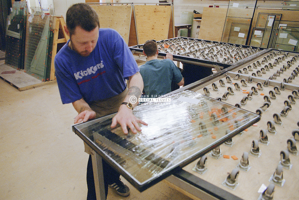 Man working in glass factory handling piece of glass,