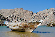A dhow is sitting in shallow water