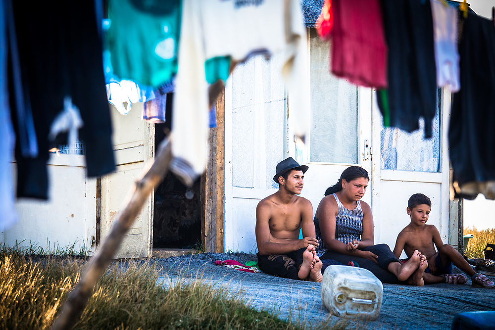 Sergio (19) and Nicoletta (21) and their son Emmanuel (7) rest outside their makeshift home in a slum built next to the Pata Rat garbage dump.                                                          © Daniel Barreto Mezzano