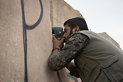 © Licensed to London News Pictures. 28/09/2014. Rabia, Iraq. A fighter belonging to the Syrian-Kurdish YPG scans Islamic State territory after several bursts of machine gun fire targeted YPG positions in the Iraqi border town of Rabia.<br /> <br /> Facing each other across the Iraq-Syria border, the towns of Al-Yarubiyah, Syria, and Rabia, Iraq, were taken by Islamic State insurgents in August 2014. Since then The town of Al-Yarubiyah and parts of Rabia have been re-taken by fighters from the Syrian Kurdish YPG. At present the situation in the towns is static, but with large exchanges of sniper and heavy machine gun fire as well as mortars and rocket propelled grenades, recently occasional close quarter fighting has taken place as either side tests the defences of the other. Photo credit: Matt Cetti-Roberts/LNP