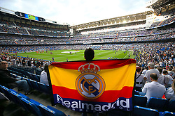 A Real Madrid fan holds a flag in the stands as the teams warm up prior to the match