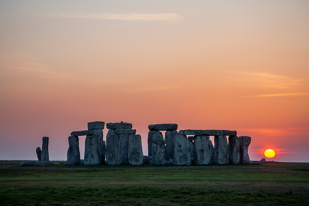 Licensing - Open Edition Prints<br /> Stonehenge is a prehistoric monument on Salisbury Plain in Wiltshire, England, two miles (3 km) west of Amesbury. It consists of an outer ring of vertical Sarsen standing stones, each around 13 feet (4.0 m) high, seven feet (2.1 m) wide, and weighing around 25 tons, topped by connecting horizontal lintel stones. Inside is a ring of smaller bluestones. Inside these are free-standing trilithons, two bulkier vertical Sarsens joined by one lintel. The whole monument, now ruinous, is oriented towards the sunrise on the summer solstice. The stones are set within earthworks in the middle of the most dense complex of Neolithic and Bronze Age monuments in England, including several hundred tumuli (burial mounds).[1]<br /> <br /> Archaeologists believe it was constructed from 3000 BC to 2000 BC. The surrounding circular earth bank and ditch, which constitute the earliest phase of the monument, have been dated to about 3100 BC. Radiocarbon dating suggests that the first bluestones were raised between 2400 and 2200 BC,[2] although they may have been at the site as early as 3000 BC.[3][4][5]<br /> <br /> One of the most famous landmarks in the United Kingdom, Stonehenge is regarded as a British cultural icon.[6] It has been a legally protected Scheduled Ancient Monument since 1882, when legislation to protect historic monuments was first successfully introduced in Britain. The site and its surroundings were added to UNESCO's list of World Heritage Sites in 1986. Stonehenge is owned by the Crown and managed by English Heritage; the surrounding land is owned by the National Trust.[7][8]<br /> <br /> Stonehenge could have been a burial ground from its earliest beginnings.[9] Deposits containing human bone date from as early as 3000 BC, when the ditch and bank were first dug, and continued for at least another 500 years.