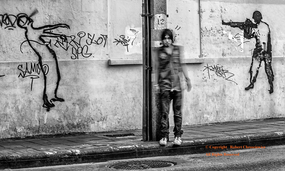Witness to an Execution (B & W): A young man's movement is captured, his face is eerily still, as he moves in between wall graffiti depicting a smiling soldiers execution of a person, Bangkok Thailand.