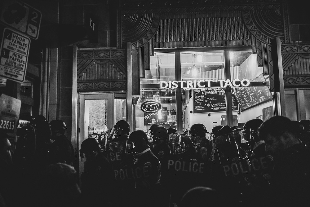 Washington DC, USA - January 19, 2017: Washington Metropolitan Police carrying riot shields walk past District Taco on F Street NW during a protests on the eve of President-elect Trump's inauguration.