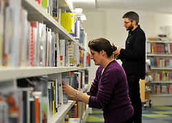 © Licensed to London News Pictures. 21/11/2011, London, UK. Staff stock the bookshelves. London's Southwark Council previews Canada Water Library its new 'super library', featuring a 150-seat theatre, restaurant and cafe, evening class space community meeting rooms and Tube station entrance and exit. The building opens to the public on November 28. Photo credit : Stephen Simpson/LNP
