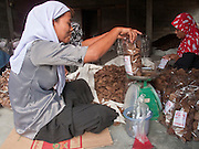 """Sept. 28, 2009 -- TANJONG DATO, THAILAND: Muslim women make fish crackers in a small hut in the Muslim village of Tanjong Dato, in the province of Pattani, Thailand. The crackers are exported to Malaysia and the cracker factory is a leading source of revenue in the community. Everybody in the village is Muslim and they say they have no problems, but the roads around the village leading to the provincial capital of Pattani are too dangerous for them to use once it gets dark. Thailand's three southern most provinces; Yala, Pattani and Narathiwat are often called """"restive"""" and a decades long Muslim insurgency has gained traction recently. Nearly 4,000 people have been killed since 2004. The three southern provinces are under emergency control and there are more than 60,000 Thai military, police and paramilitary militia forces trying to keep the peace battling insurgents who favor car bombs and assassination.   Photo by Jack Kurtz / ZUMA Press"""