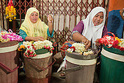"""Sept. 24, 2009 -- PATTANI, THAILAND: Muslim women make flower garlands they sell to Thai Buddhists for religious purposes in the night market in Pattani, Thailand.  Thailand's three southern most provinces; Yala, Pattani and Narathiwat are often called """"restive"""" and a decades long Muslim insurgency has gained traction recently. Nearly 4,000 people have been killed since 2004. The three southern provinces are under emergency control and there are more than 60,000 Thai military, police and paramilitary militia forces trying to keep the peace battling insurgents who favor car bombs and assassination.   Photo by Jack Kurtz / ZUMA Press"""