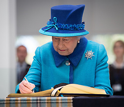 © Licensed to London News Pictures . 14/11/2013 . Manchester , UK . The Queen signs the guest book . Queen Elizabeth II and the Duke of Edinburgh visit the Coop building at 1 Angel Square , Manchester , this morning ( 14th November 2013 ) . Photo credit : Joel Goodman/LNP