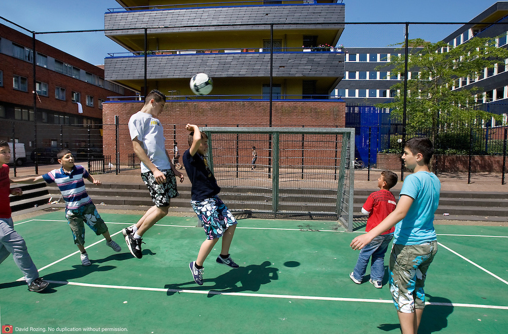Nederland Rotterdam 24-05-2009 20090524 Foto: David Rozing .                                                                                    .Achterstandswijk Bloemhof, groepje jongeren spelen voetbal op pleintje  straatbeeld, stadbeeld Youth playing soccer on playground court .Foto: David Rozing