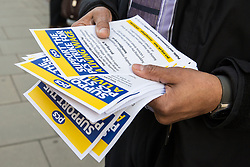 London, UK. 13th February, 2019. A Public & Commercial Services (PCS) union member hands out leaflets on the picket line with outsourced worker colleagues who walked out from the Department of Business, Energy and Industrial Strategy (BEIS) for their second day of strike action to demand the London Living Wage and an end to outsourcing. Union members handed out strike-themed cakes to supporters in return for donations to the strike fund.