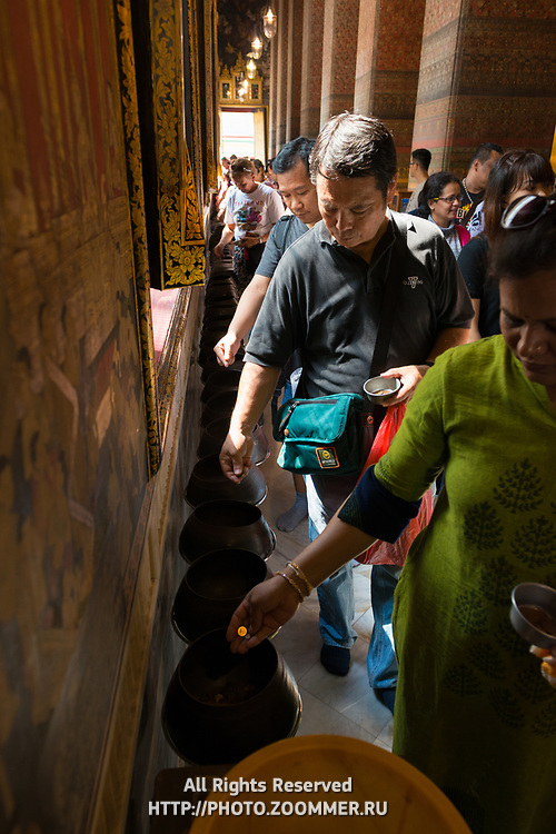 Tourists donating money in the Temple of the Reclining Buddha, Bangkok, Thailand