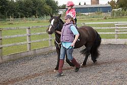Girl having riding lesson.