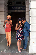 An Indian holy man walks past an amorous couple as they  check their telephone in Connaught Place, New Delhi, India